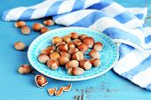 Hazelnuts on plate on wooden background