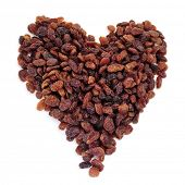 a pile of sultana raisins forming a heart on a white background