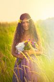 smiling beautiful woman with long curly hair hold in hand a bouquet of wild flowers in romantic dress stand in grass field