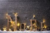 Wooden NOEL with Christmas lights on snow
