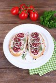 Sandwiches with salami on plate on napkin on wooden background