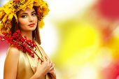 Beautiful young woman with yellow autumn wreath and red berries