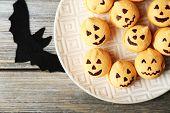 Tasty Halloween macaroons on plate, on wooden table