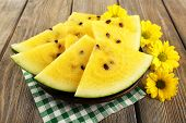 Slices of yellow watermelon on checkered napkin and yellow flowers on wooden background