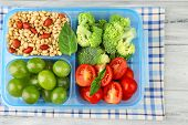 Tasty vegetarian food in plastic box on wooden table