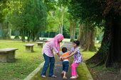 Children playing at outdoor garden park. Happy Southeast Asian family living lifestyle.