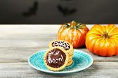 Tasty Halloween cookies on plate, on wooden table