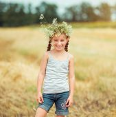 happy little girl with a wreath on her head on the field