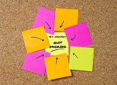 image of tobacco smoke  - yellow post it note on cork board and marker arrow as reminder of quit smoking stop cigarettes nicotine and tobacco habit New Year resolution and start healthy life concept - JPG