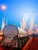 stock photo of petroleum  - beautiful lighting of oil refinery plant in heavy petrochemical industry and container truck transportation of petroleum - JPG