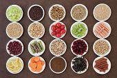 Large diet health food selection in porcelain bowls over lokta paper background.