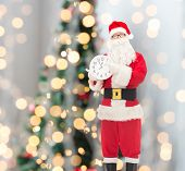 christmas, holidays and people concept - man in costume of santa claus with clock showing twelve pointing finger over tree lights background