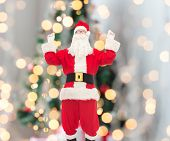 christmas, holidays and people concept - man in costume of santa claus having fun over tree lights background