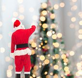 christmas, holidays and people concept - man in costume of santa claus pointing finger from back over tree lights background