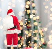 christmas, holidays and people concept - man in costume of santa claus with bag from back over tree lights background