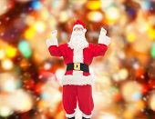 christmas, holidays and people concept - man in costume of santa claus having fun over red lights background