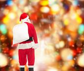 christmas, holidays and people concept - man in costume of santa claus with bag from back over red lights background