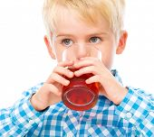Little boy is drinking cherry juice using straw, isolated over white