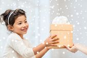 holidays, christmas, childhood and people concept - smiling little girl with gift box at home
