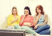 home, technology and friendship concept - three sad teenage girl watching tv at home and eating popcorn