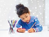 creativity, childhood and people concept - little girl with pencils drawing at home