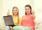 friendship, technology and internet concept - two smiling teenage girls with laptop computer at home showing thumbs up