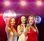 new year celebration, friends, bachelorette party, birthday concept - three women in evening dresses with cocktails and disco ball