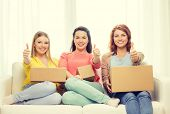 transportation, post and friendship concept - three smiling teenage girls with cardboard boxes at home showing thumbs up