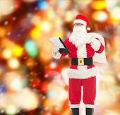 christmas, holidays and people concept - man in costume of santa claus with notepad and bag over red lights background