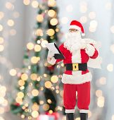christmas, holidays and people concept - man in costume of santa claus with notepad and bag over tree lights background