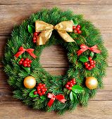 Christmas decorative wreath with leafs of mistletoe on wooden background