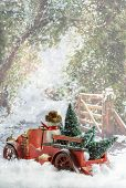 Vintage red truck transporting Christmas trees in snowy country lane
