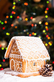 foto of gingerbread house  - gingerbread house over defocused lights of Chrismtas decorated fir tree - JPG