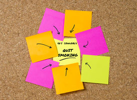picture of tobacco smoke  - yellow post it note on cork board and marker arrow as reminder of quit smoking stop cigarettes nicotine and tobacco habit New Year resolution and start healthy life concept - JPG