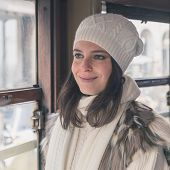 pic of tram  - Beautiful young woman wearing ecological fur poses on a tram - JPG