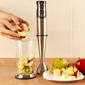 stock photo of blender  - Hands chefs put the fruit in the blender to prepare the smoothie on the table - JPG