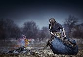 image of spring-cleaning  - Old rural woman burning fallen leaves spring cleaning in the garden - JPG