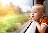 foto of passenger train  - Little boy traveling in train looking outside the window - JPG