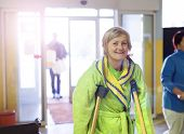 picture of hospital gown  - Senior woman injured walking through hospital corridor with crutches - JPG