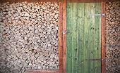 stock photo of wooden shack  - Retro photo of old rustic wooden door with firewood - JPG