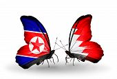 stock photo of bahrain  - Two butterflies with flags on wings as symbol of relations North Korea and Bahrain - JPG