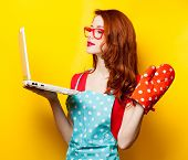 picture of oven  - Young housewife with computer and oven gloves on yellow background - JPG