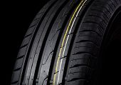 stock photo of asymmetric  - tire with asymmetric tread on a black background - JPG