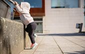picture of hoodie  - Little girl with sneakers and hoodie training hard with a metal railing in a city square - JPG