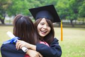 pic of graduation  - young female graduate hugging her friend at graduation ceremony - JPG