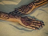 stock photo of finger-painting  - picture of beauty long fingers with black manicure and mehendi on sand close up - JPG