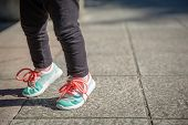 picture of leggins  - Closeup of little girl legs with sneakers and black leggins training outdoors - JPG
