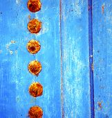 picture of nail paint  - stripped paint in the blue wood door and rusty nail - JPG