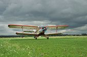 picture of biplane  - Old propeller biplane taking off from the rough airstrip with stormy clouds on the background - JPG