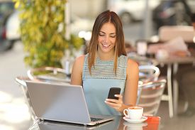 foto of self-employment  - Happy entrepreneur working with a phone and laptop in a coffee shop in the street - JPG